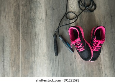 Sport shoes and jumping rope on wooden background