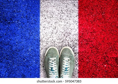 Sport shoes on asphalt with french flag, election concept
