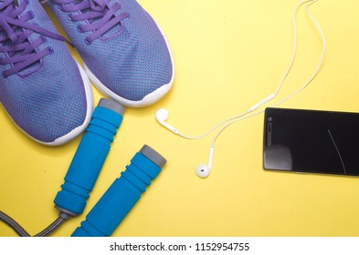 Sport shoes with skipping rope on yellow background. top view. The concept of active recreation and healthy lifestyle. Selective focus.