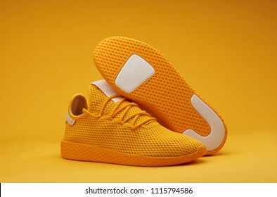 Sport shoes theme in yellow color. Pair of tennis shoes