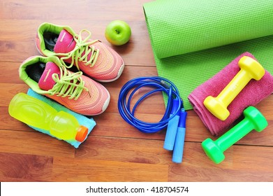 Sport shoes and water with set for activities on wooden floor.