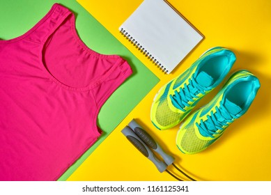 Sport shoes, woman's top bra, white blank notebook and skipping rope on colorful yellow and green backgroundon, copy space. Top view, flat lay. Sport and healthy lifestyle concept, flat lay