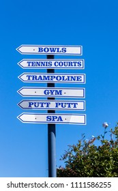Sport signs directions, for bowls, tennis, trampoline, gym,putt putt,spa on outdoor pole against blue sky.