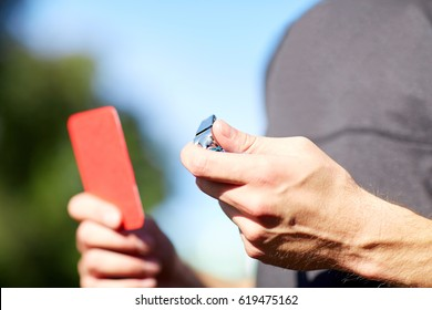sport, soccer, caution, game and people concept - referee hands with whistle and red card on football field