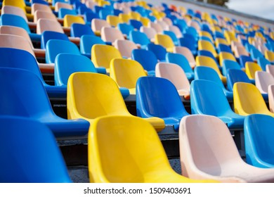 Sport stadium seats for fans.Bleachers for spectators in outdoor amphiteater.Empty space with many plastic chairs for fans