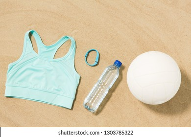 sport, summer and objects concept - sports top, ball, fitness tracker and water bottle on beach sand