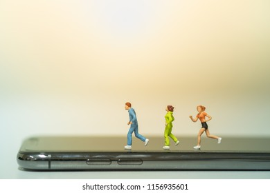 Sport and technology concept. Group of runner miniature figures running on smart phone.
