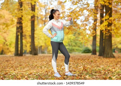 sport, technology and healthy lifestyle concept - young woman with earphones and fitness tracker in autumn park