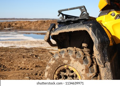 Sport, tourism and activity - Closeup motorised quadricycle in dirt on frozen the rivers a background