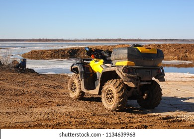 Sport, tourism and activity - Motorised quadricycle in dirt on frozen the rivers a background