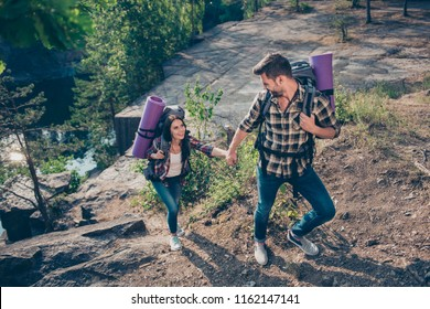Sport, tourism, lifestyle. Adorable nice lovely spouses climbing, wearing casual checkered shirts and jeans. Spending free time in wild wood, girl holding guy's hand, following him