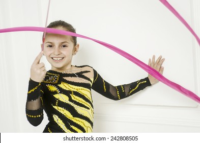 Sport training beautiful girl with Pink Rhythmic gymnastics ribbon in white room jumping and doing professional exercises