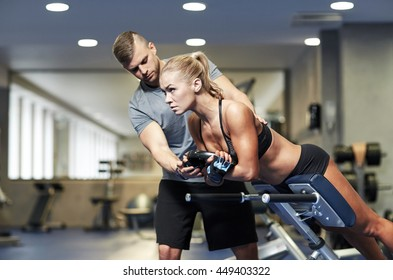 sport, training, fitness, lifestyle and people concept - young woman with personal trainer flexing back and abdominal muscles on bench in gym