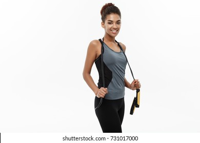Sport, training, lifestyle and Fitness concept - portrait of beautiful happy African American woman exercising with jumping rope. Isolated on white studio background.