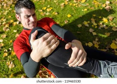 Sport training tibia fracture injury. Male athlete grabbing painful leg.