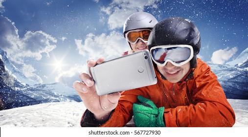 Sport and travel backgrounds. Winter, ski, snow and fun - family enjoying ski holiday. Mobile photo. Selfy.