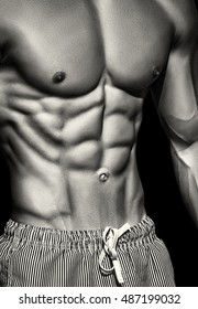 Sport. Unrecognizable strong man showing his perfect abs -- black and white toned and stylized photo