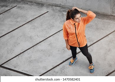 Sport, urban lifestyle and recreation concept. Upper view fit and appealing sportswoman in orange running jacket, leggings, look aside, decide which direction run, runner on her daily exercise route