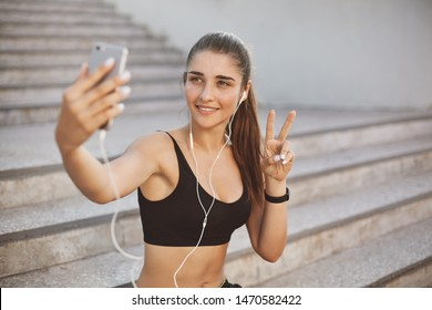 Sport, urban lifestyle, technology concept. Cheerful athletic woman in fitness tracker and activewear, listen music wired earphones, taking selfie as sit concrete staircases outdoors after running