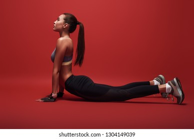 Sport is the way of her life. Sportswoman lying over red background, stretching her body