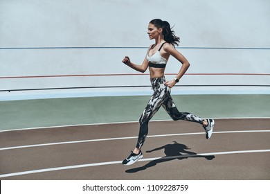 Sport is the way of life. Full length of young woman in sports clothing jogging while exercising outdoors