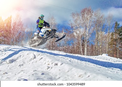 Sport white snowmobile jump. Clear sunny winter day. Concept quick movement. Extreme sport background for any purposes. Copy space.