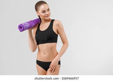 Sport woman in black slim with mat for joga. Studio shot.