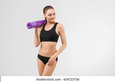 Sport woman in black slim with mat for joga