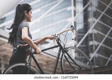 Sport woman is carrying her bike up the stair