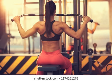 Sport woman doing body exercise for chest and back on machine in gym, back view