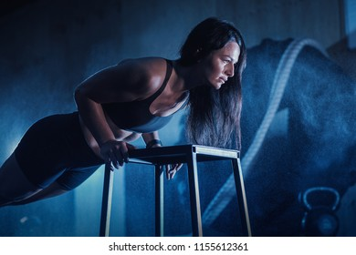 Sport woman doing push-ups on black background in the gym. Fitness Workout. Young girl doing an exercise peacock pose.