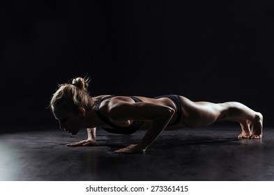 Sport woman doing push-ups on black background