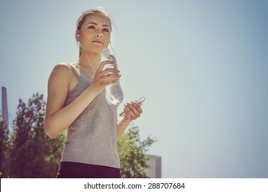 Sport woman drinking water and listening to music with headphones in the phone in the park outdoors