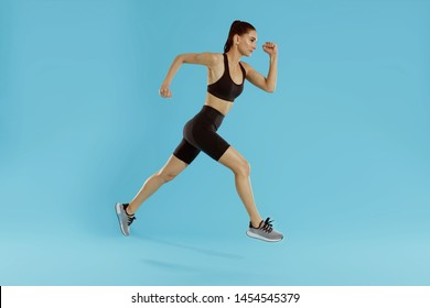 Sport woman with fit body jumping and running on blue background. Full length portrait of sporty girl, female runner in fashionable sportswear exercising at studio