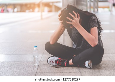 Sport Woman with hand on her head getting headache and depression from sport injury. Loser Female is exhausted and depressed sitting on the street with sadness.
