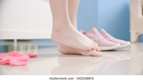 sport woman has athletes foot and itching her barefoot