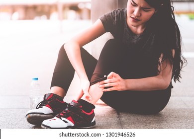 Sport Woman having pain Injury on Ankle from running concept, asian woman holding her ankle and massaging on her leg for muscle strain