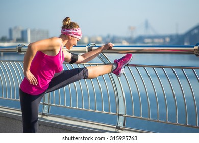 Sport woman having stretching during training outside in city quay in the morning