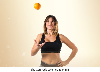 Sport woman playing with an orange
