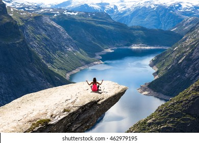 Sport woman posing on Trolltunga. Happy woman enjoy beautiful lake and good weather in Norway.