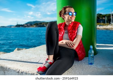 Sport woman in red vest and sneakers sitting near the green lighthouse on the beach
