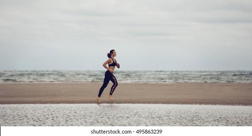 Sport woman runnig on the beach