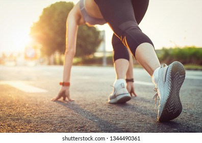 Sport woman in running start pose on the city street during sunrise with the blurry background. Sport tight clothes and pant.