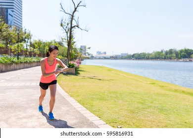 Sport Woman running and using smart watch in benjakitti park