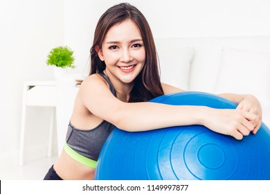 Sport woman in sportswear sitting relax and do fitness exercise with blue fitball at home.Diet concept.Fitness and healthy lifestyle