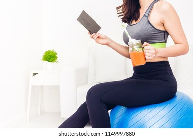 Sport woman in sportswear sitting relax reading a book and drink fresh juice after workout on blue fitball at home.Diet concept.Fitness and healthy lifestyle