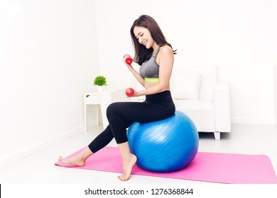 Sport woman in sportswear sitting relax and do fitness exercise with dumbbell and blue fitball at home.Diet concept.Fitness and healthy lifestyle