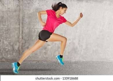 Sport woman starting running. young woman jogging front cement wall
