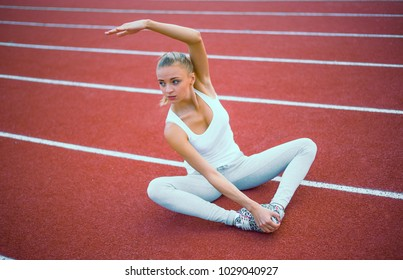 Sport woman stretching hand in sport court.Sport girl stretching arm in sport running arena with many tracks.