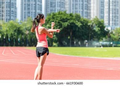 Sport woman stretching hand in sport stadium
